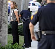 An activist is taken into custody by Palm Beach police during a protest on Royal Palm Way.