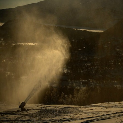 In a warmer future of unyielding blue skies, snow machines like this one, at work in Norway, will be increasingly employed to produce ski-able snowpack. Photo courtesy of Flickr user Rsms.