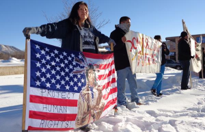 Belinda Ayze, Navajo, of Flagstaff, Arizona, holds a protest sign during a rally on December 21 to oppose snowmaking with treated wastewater on the San Francisco Peaks.