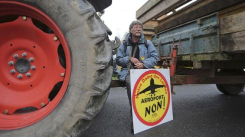 """This Nov. 17, 2012 file photo shows a demonstrator holding a sign reading: """"Airport No"""", on a road near Notre Dame des Landes, western France, as part of a protest against a project to build an international airport, in Notre Dame des Landes, near Nantes. An unlikely alliance of anarchists and beret-wearing farmers is creating a headache for President Francois Hollande's beleaguered government by mounting an escalating Occupy Wall Street-style battle that has delayed construction on the ambitious airport near the city of Nantes for months. (AP Photo/David Vincent, File) (The Associated Press)"""