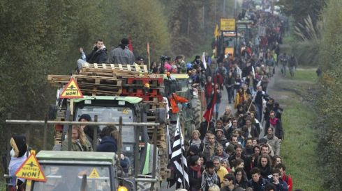 This Nov. 17, 2012 file photo shows demonstrators walking along a road near Notre Dame des Landes, western France, as part of a protest against a project to build an international airport, in Notre Dame des Landes, near Nantes. An unlikely alliance of anarchists and beret-wearing farmers is creating a headache for President Francois Hollande's beleaguered government by mounting an escalating Occupy Wall Street-style battle that has delayed construction on the ambitious airport near the city of Nantes for months. (AP Photo/David Vincent, File) (The Associated Press)