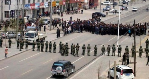 Chinese security personnel face off protesters on a street of Xilinhot in northern China's Inner Mongolia province.