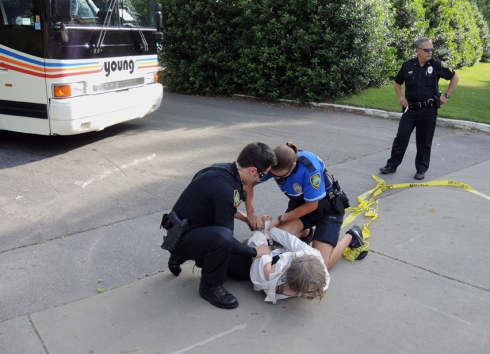 A local organizer with Katuah Earth First! is thrown to the ground and arrested in front of the bus.
