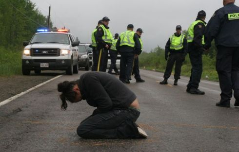 Susanne Patles in prayer, as New Brunswick RCMP confer. (Photo: M. Howe)