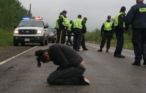 Susanne Patles in prayer, as New Brunswick RCMP confer. (Photo: M. Howe)