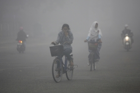 Residents of Sampit, Indonesia, bike through smog in Sept. 2012. (Photo: Reuters)