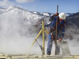 A worker checks a dipstick to check water levels and temperatures in a series of tanks at a fracking operation at a gas drilling site outside Rifle, Colorado. (AP/Brennan Linsley)