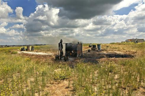 A farmhand stands nearby the home-made oil refinery, consisting of a rusted tank connected to a few tubes.