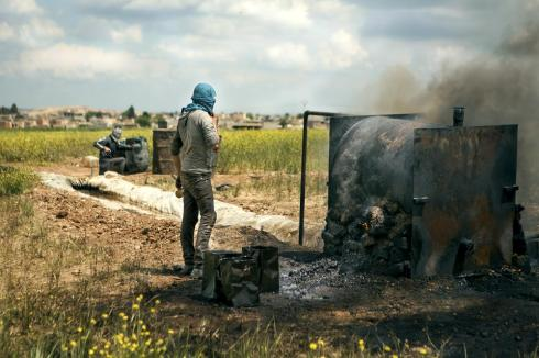 Abu Zechariah's sons work with their father, with one standing by the refinery and the other collecting the produced diesel in an oil barrel.